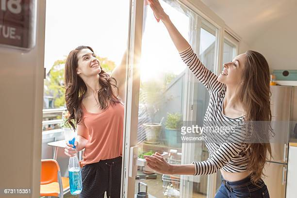 Two women cleaning window together
