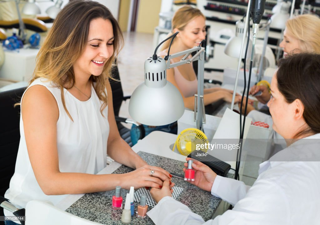Two women clients having manicure done in nail salon : Stock Photo