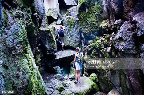 two women climb through crack in the ground, a volcanic fissure near christmas valley, oregon. - free climbing stock pictures, royalty-free photos & images