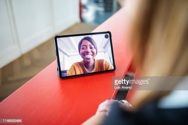 two women colleagues on video chat in office - video conference stock pictures, royalty-free photos & images