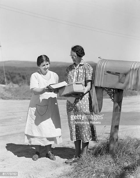two women collect mail from country mailbox. - domestic mailbox stock pictures, royalty-free photos & images