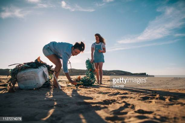 two women collecting garbage on the beach - inquinamento ambientale foto e immagini stock