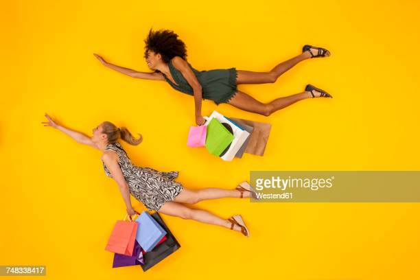 two women coming from a shopping spree, carrying shopping bags - voler photos et images de collection