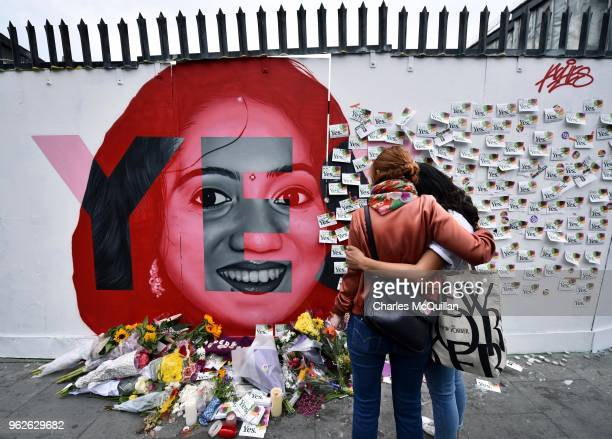 Two women console one another as they look at written notes left on the Savita Halappanavar mural as the results in the Irish referendum on the 8th...
