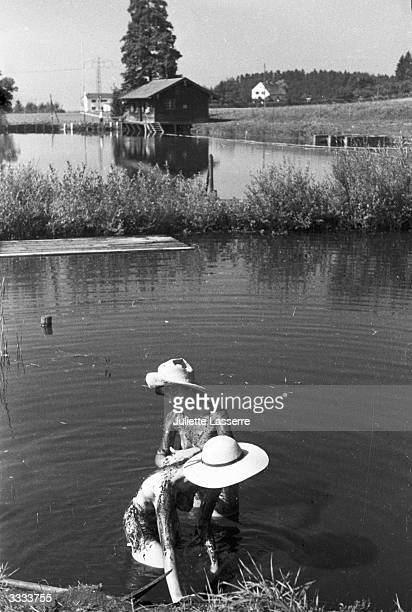Two women cooling off with a muddy massage in a lake at a sauna in Munich