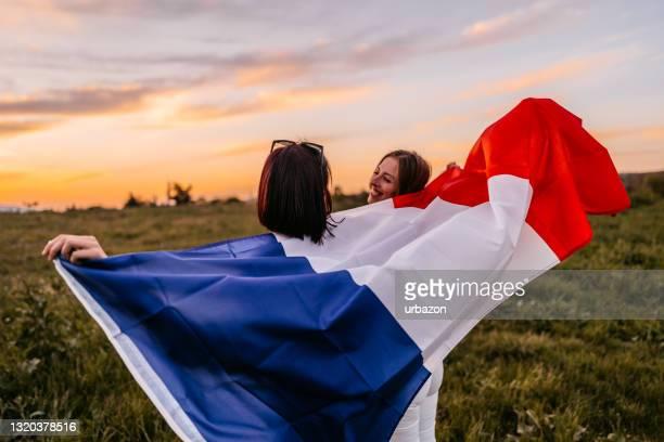 twee vrouwen die zich met vlag van frankrijk op weide bedekken - franse vlag stockfoto's en -beelden