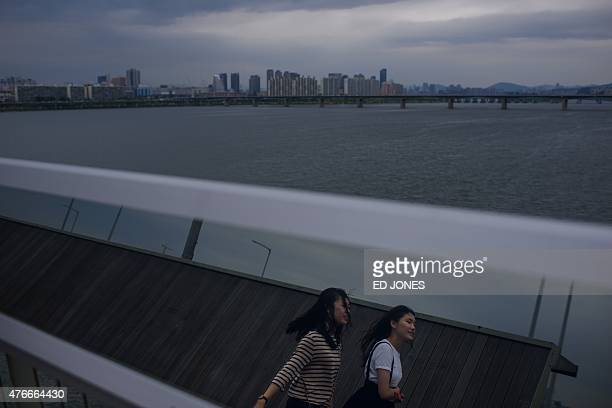 Two women cross the Mapo bridge over the Han river before the Seoul city skyline on June 11 2015 South Korea's outbreak of the potentially deadly...