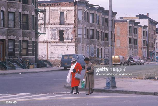 Two women crossing street in ghetto South Bronx New York