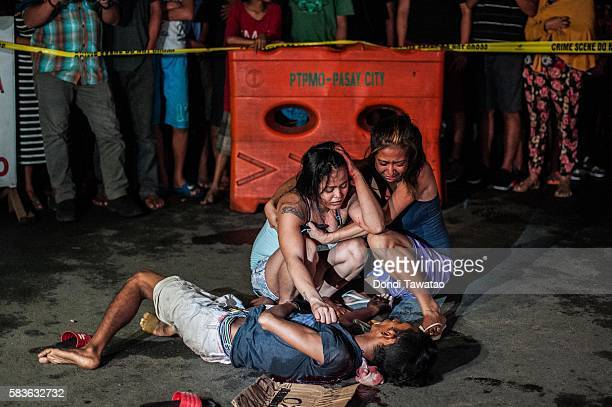 Two women cry in grief after armed assailants in a motorcycle shot their loved one in a main thoroughfare on July 23 2016 in Manila Philippines The...