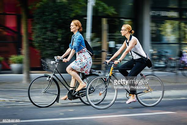 two women cycling in the city - fahrrad stock-fotos und bilder