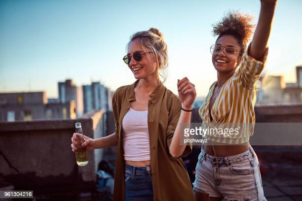 two women dancing at the party. - roof stock photos and pictures