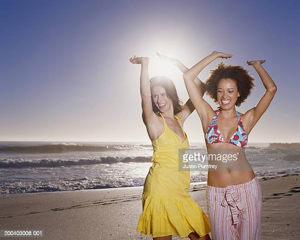 Two women dancing on beach at sunset, arms raised, smiling