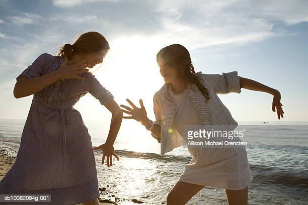 two women dancing on beach at sunset - dreiviertelansicht stock-fotos und bilder