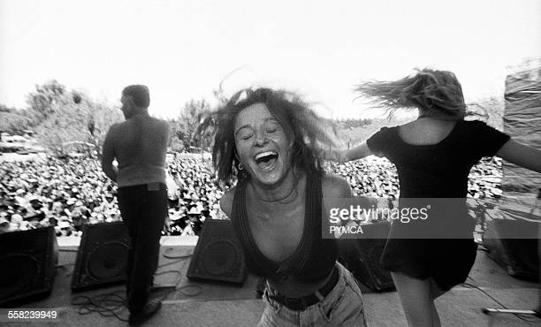 Two women dancing on stage while a security man sprays the crowd with water at Bindoon Festival WAustralia 1990s