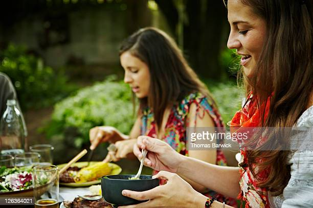 Two women dining at table in backyard
