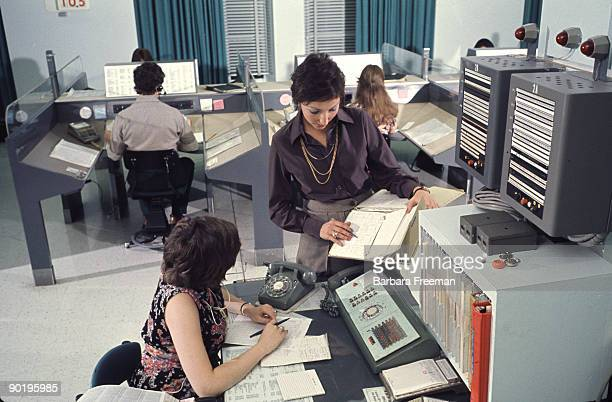 Two women discuss a report while working in a computerequipped office Pittsburgh PA ca 1974