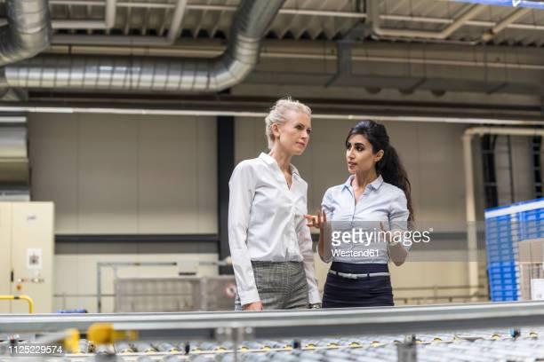 two women discussing at conveyor belt in factory - weibliche angestellte stock-fotos und bilder