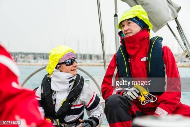 twee vrouwen bespreken op zeilboot - reddingsvest stockfoto's en -beelden