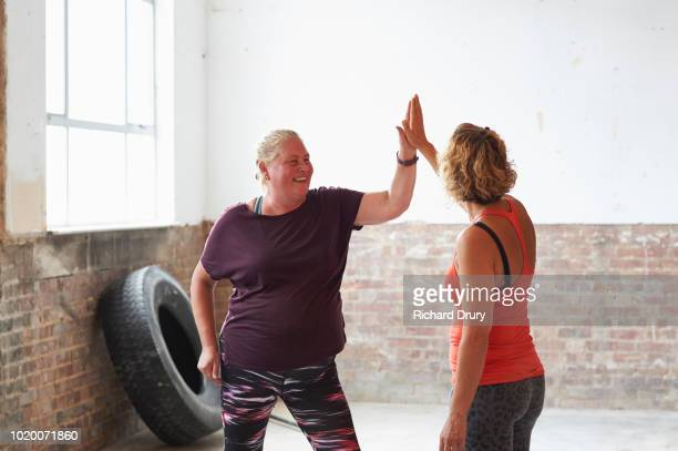 two women doing a high-five during an exercise class at the gym - two people stock pictures, royalty-free photos & images