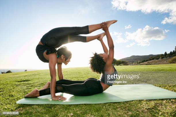 two women doing acro yoga in green field