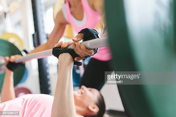 Two women doing barbell bench presses in a power rack