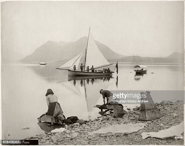 Two Women Doing Laundry at Shore of Lake Maggiore with Sailboat and Sasso di Ferro Mountain in Background Lombardy Italy circa 1880