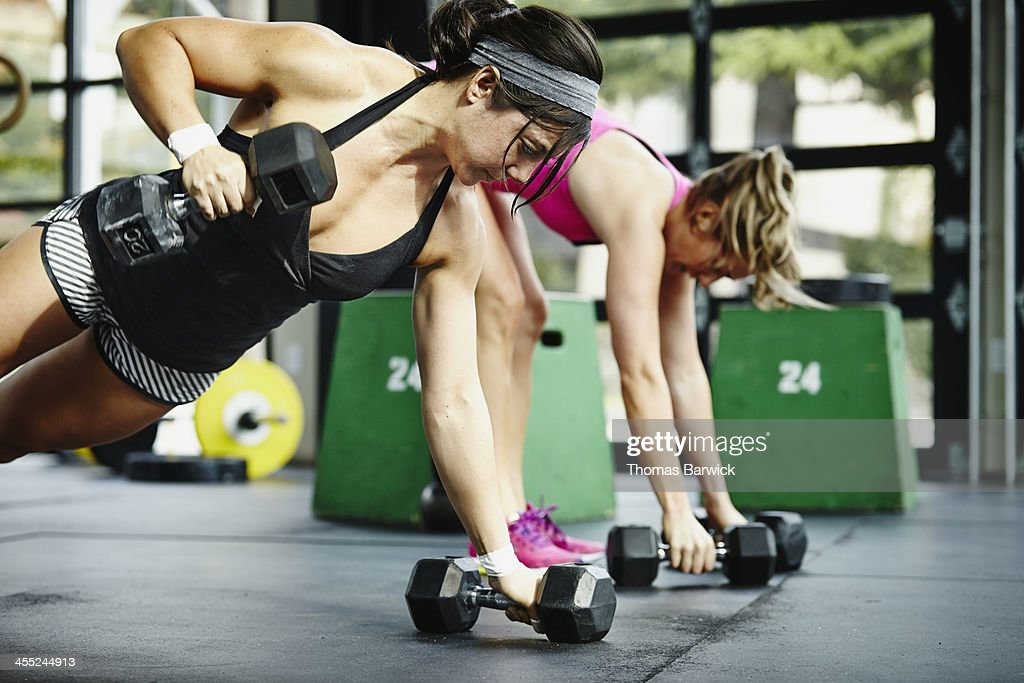 Two women doing pushups with dumbbells in gym : ストックフォト