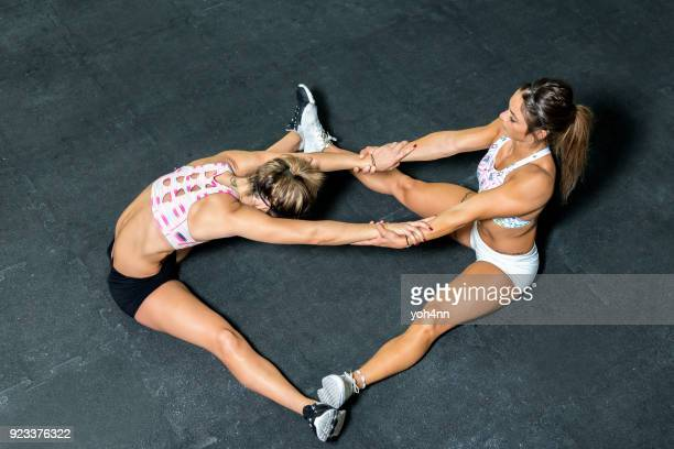 two women doing stretching - legs spread woman stock photos and pictures