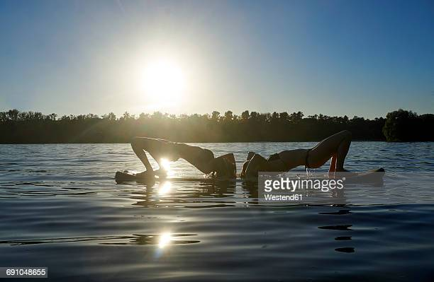 two women doing yoga on paddleboard at sunset - sport aquatique photos et images de collection