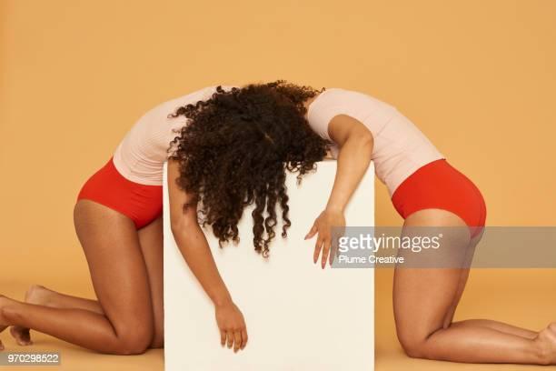 two women draped over a white plinth - menstruation gesundheitswesen und medizin stock-fotos und bilder