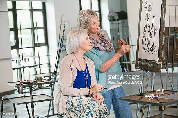 Two women drawing in art class