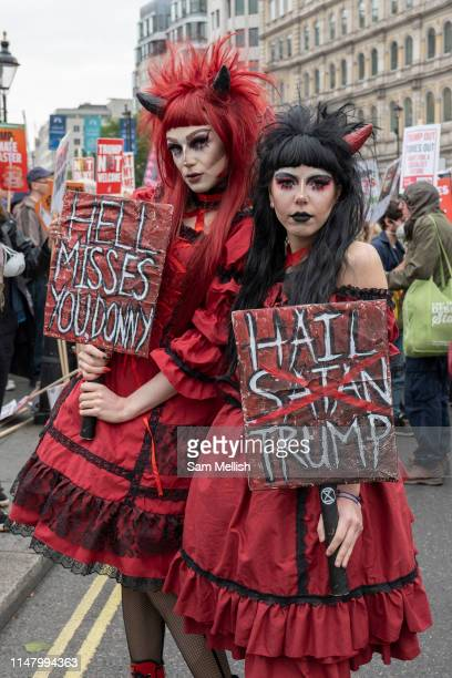 Two women dressed as red devils during a demonstration against US President Donald Trump's state visit to the UK on the 4th June 2019 in London in...