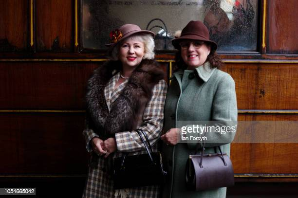 Two women dressed in 1940's clothes one for pictures at Pickering Station during the North Yorkshire Moors Railway 1940's Wartime Weekend event on...