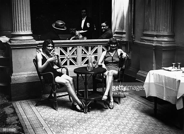 Two women dressed in bathing suits enjoying a drink during the Paris heat wave