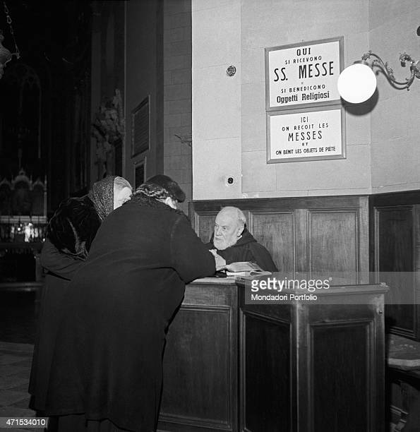 'Two women dressed in black standing at the counter where a franciscan friar seated receives people asking for Masses for the souls or the blessing...