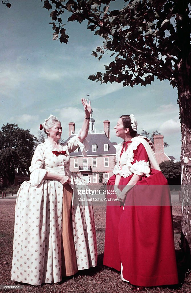 Two women dressed in Colonial dresses, reenact daily life in Colonial Williamsburg, Virginia. A living history of life in circa 1700's.