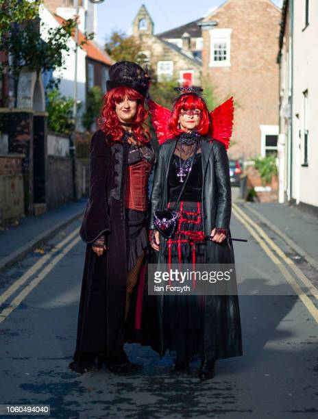 Two women dressed in extravagant goth clothing pose for a photograph during Whitby Goth Weekend on October 28 2018 in Whitby England Whitby Goth...