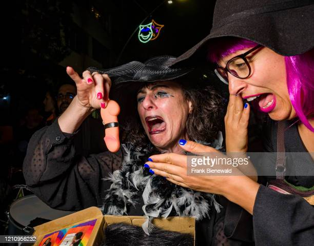 Two women, dressed up in mourning clothes, carrying a dildo and crying, partying in the streets during the funeral procession Burial of the Sardine,...