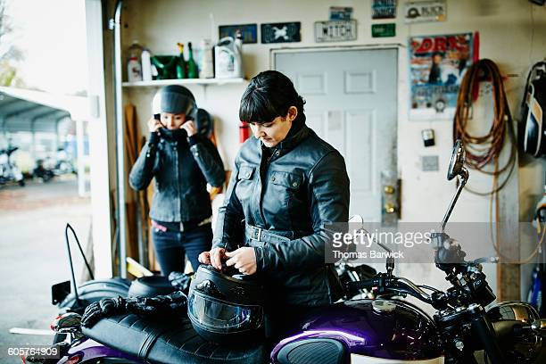 Two women dressing in protective gear before ride