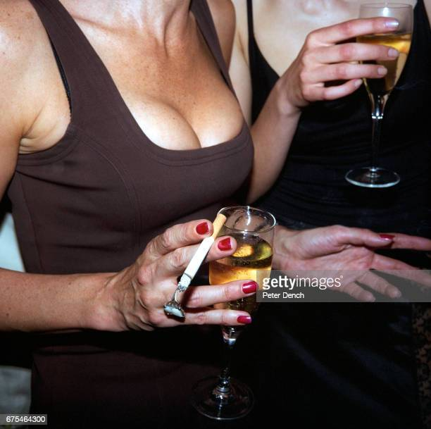 Two women drink champagne at a health resort launch party in central London April 1998