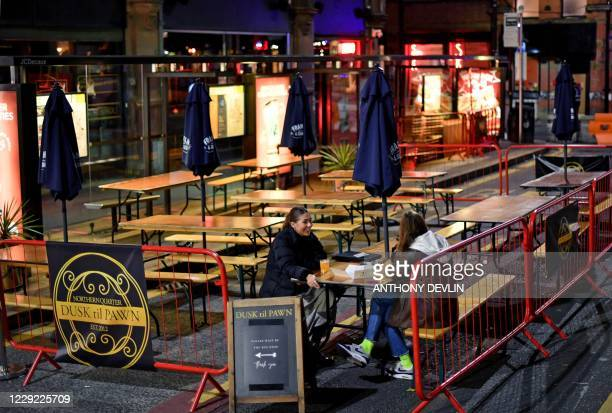 Two women drink in an empty bar on Dale Street in Manchester city centre northwest England ahead of new coronavirus restrictions coming into force on...