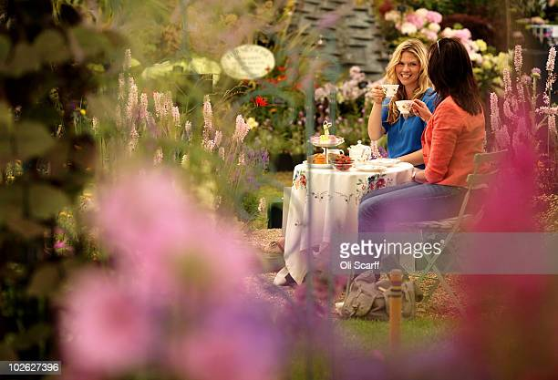 Two women drink tea in a show garden during the press preview day for the Hampton Court Palace Flower Show on July 5 2010 in London England The 21st...