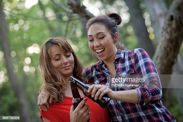 Two women drinking beer by campfire