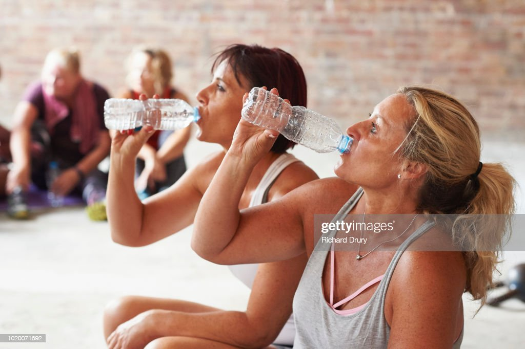 Two women drinking from water bottles in the gym : Stock Photo