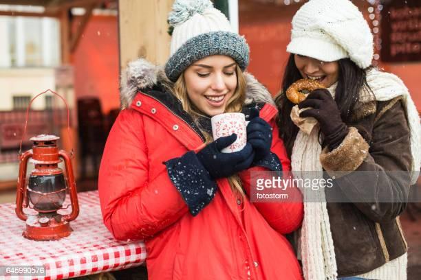 Zwei Frauen trinken heißes Getränk am Weihnachtsmarkt