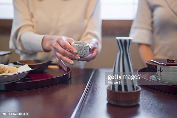 two women drinking sake during traditional japanese lunch - saki stock photos and pictures