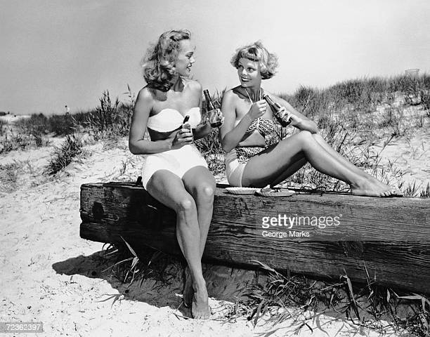 Two women drinking soda on beach