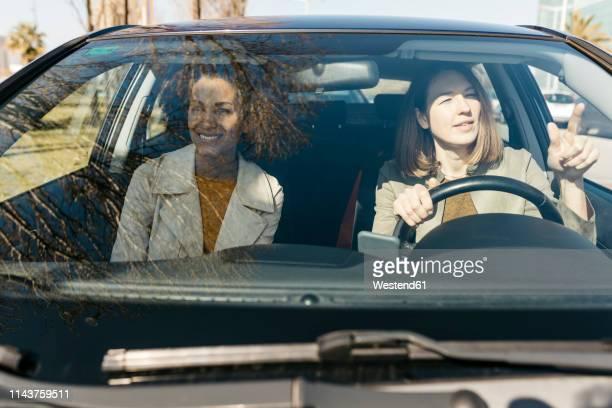 two women driving in a car through the city - conductor oficio fotografías e imágenes de stock
