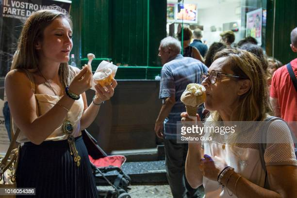 Two women eat ice cream in front of the Cesare ice cream shop during the nightlife in the Via Marina The Via Marina of Reggio Calabria consists of...