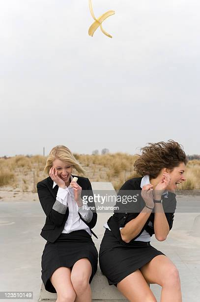 Two women eating bananas with one peel tossed in mid-air